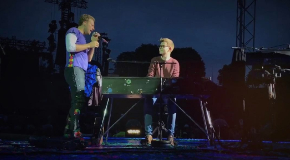 Chris Martin with fan from audience, Ferdinand Schwartz, on piano